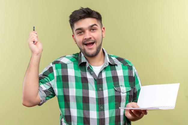 Молодой красивый парень в клетчатой рубашке с радостью нашел решение проблемы, держа ручку и тетрадь над стеной цвета хаки