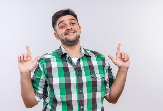 Молодой красивый парень в клетчатой рубашке, счастливо глядя вверх, с указательными пальцами, стоящими над белой стеной