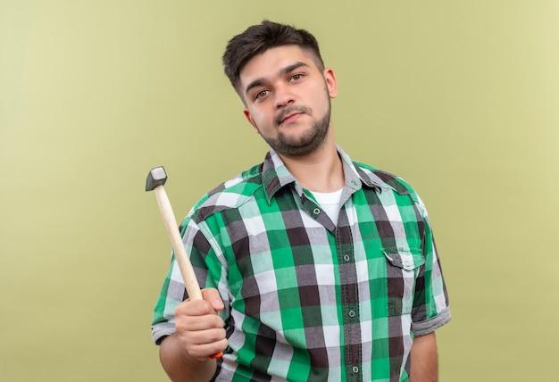 Giovane ragazzo bello che indossa la camicia a scacchi che tiene il martello in piedi sopra la parete cachi