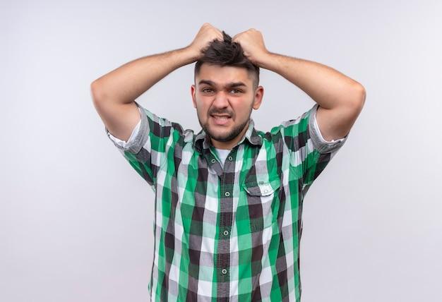 Молодой красивый парень в клетчатой рубашке держит голову, глядя по горло, стоя у белой стены