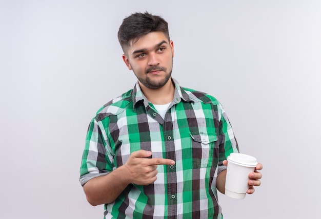 Young handsome guy wearing checkered shirt looking appraising besides pointing to plastik coffee cup standing over white wall