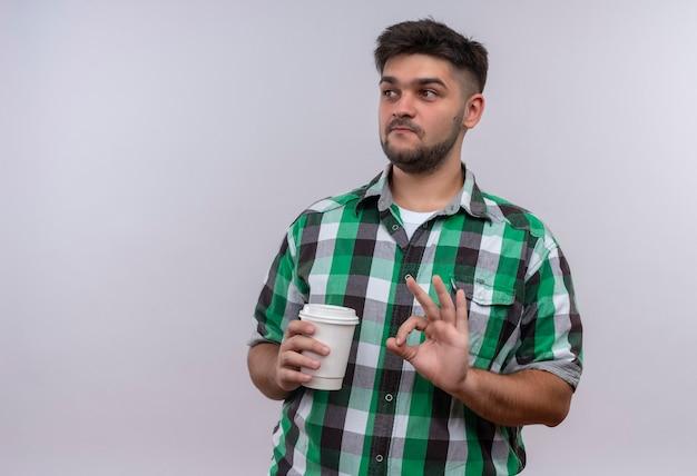 Giovane bel ragazzo che indossa la camicia a scacchi guardando oltre a lodare il caffè in piedi sul muro bianco
