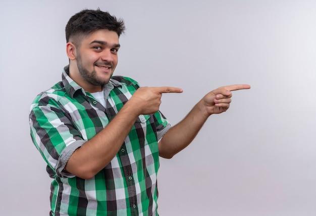 Молодой красивый парень в клетчатой рубашке, счастливо смотрящий влево, с указательными пальцами, стоящими над белой стеной