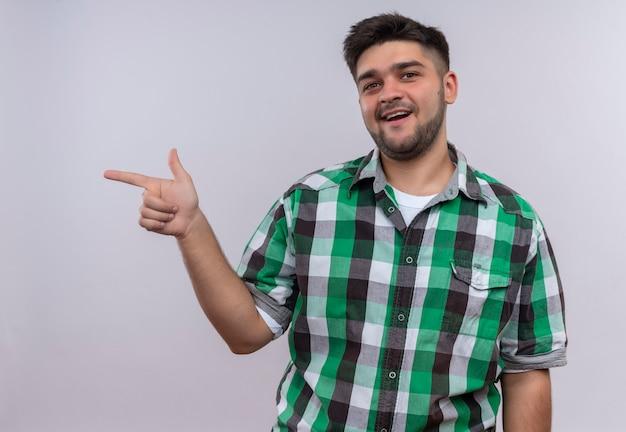 白い壁の上に立っている人差し指で右を指して幸せそうに見える市松模様のシャツを着ている若いハンサムな男