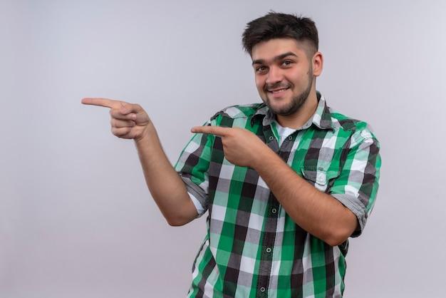 Молодой красивый парень в клетчатой рубашке, счастливо глядя вправо, с указательными пальцами, стоящими над белой стеной