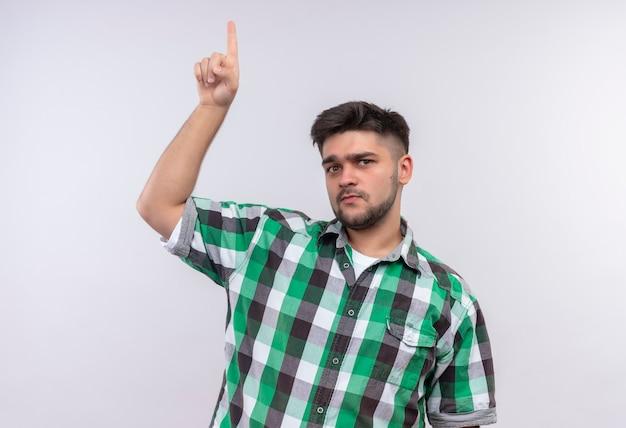 白い壁の上に立っている人差し指で上向きに見ている市松模様のシャツを着ている若いハンサムな男