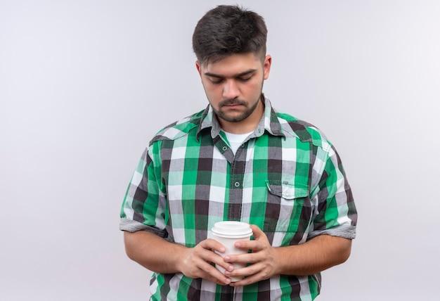 Giovane bel ragazzo che indossa la camicia a scacchi guardando tristemente verso il basso sulla sua tazza di caffè di plastica in piedi sopra il muro bianco