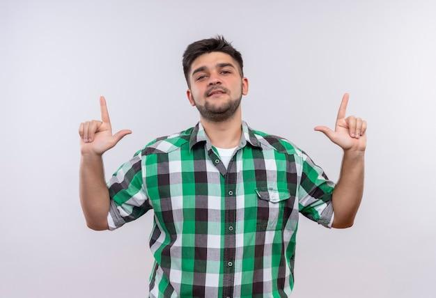 Молодой красивый парень в клетчатой рубашке, серьезно смотрящий вверх, с указательными пальцами, стоящими над белой стеной