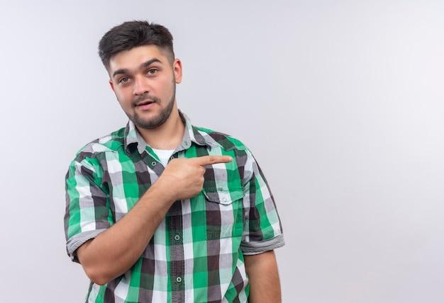 白い壁の上に立っている右手の人差し指で左を指して驚いて見える市松模様のシャツを着ている若いハンサムな男