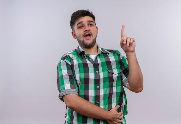 白い壁の上に立っている人差し指で上向きに驚いて見える市松模様のシャツを着ている若いハンサムな男