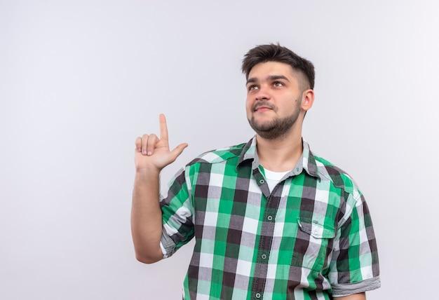 白い壁の上に立って人差し指をやって思慮深く見上げている市松模様のシャツを着ている若いハンサムな男