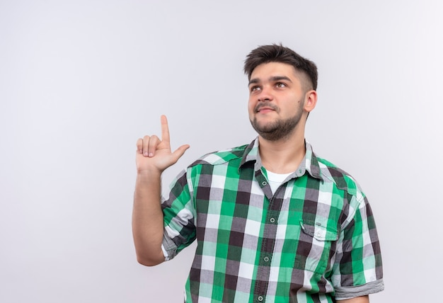 Young handsome guy wearing checkered shirt looking thoughtfully up doing forefinger up standing over white wall