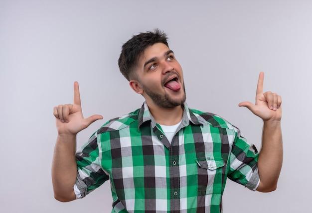 Молодой красивый парень в клетчатой рубашке смотрит вверх, игриво показывая язык, делая указательные пальцы вверх, стоя над белой стеной
