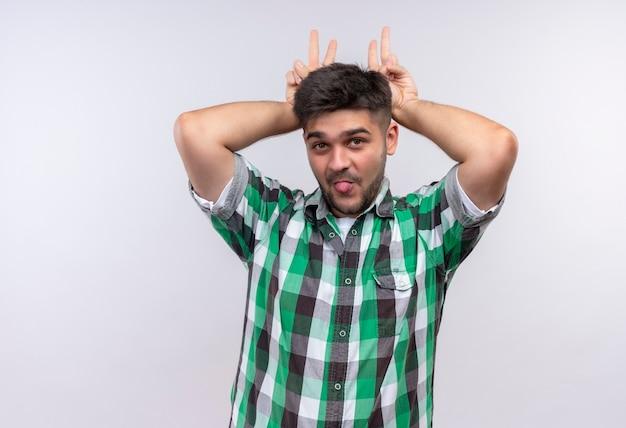 Giovane ragazzo bello che indossa la camicia a scacchi scherzosamente facendo le corna e mostrando la lingua in piedi sul muro bianco