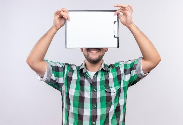 ふざけて笑顔と白い壁の上に立っているクリップボードの後ろに隠れている市松模様のシャツを着ている若いハンサムな男