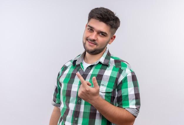 Молодой красивый парень в клетчатой рубашке показывает знак траха со средним пальцем, стоящим над белой стеной