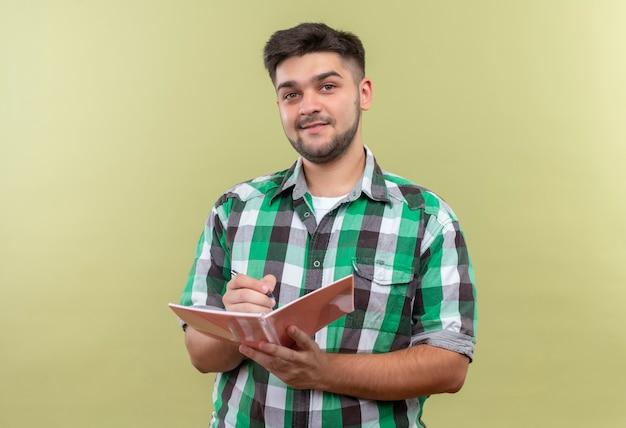 Giovane ragazzo bello che indossa la camicia a scacchi elegantemente andando a scrivere sul quaderno in piedi sopra il muro color cachi