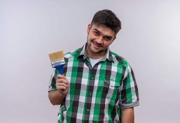 Giovane ragazzo bello che indossa la camicia a scacchi sorridente tenendo il pennello in piedi sul muro bianco
