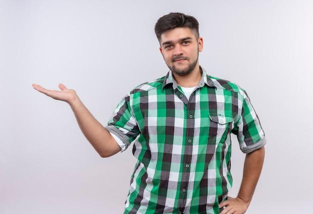 Giovane ragazzo bello che indossa la camicia a scacchi sorridente che punta a destra con la mano in piedi sul muro bianco