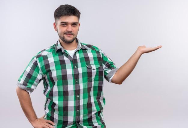 Молодой красивый парень в клетчатой рубашке улыбается, указывая налево, с рукой, стоящей над белой стеной