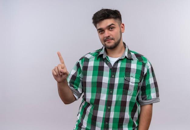 白い壁の上に立っている人差し指で上向きに笑顔の市松模様のシャツを着ている若いハンサムな男