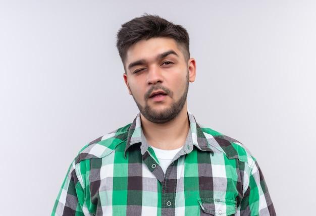 체크 무늬 셔츠를 입고 젊은 잘 생긴 남자가 흰 벽 위에 서있는 눈을 깜박이는 피곤