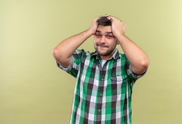 カーキ色の壁の上に立っている未定の格子縞のシャツを着ている若いハンサムな男
