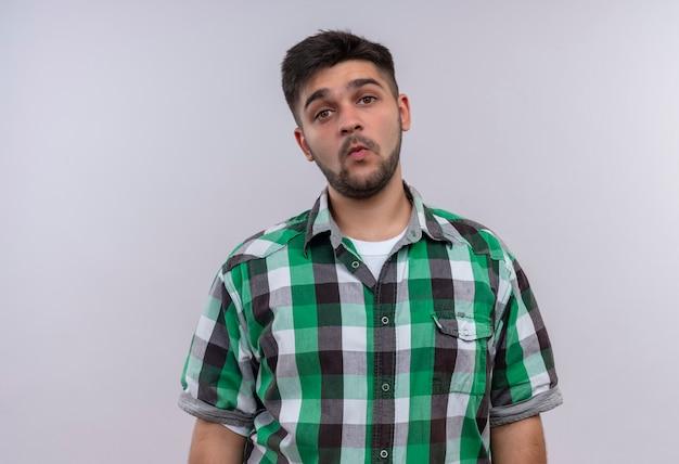 市松模様のシャツを着た若いハンサムな男は白い壁の上に立って笛を吹く