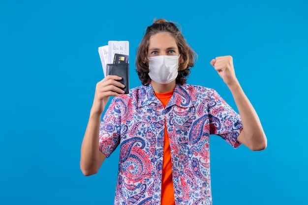 Молодой красивый парень в лицевой защитной маске, держащий авиабилеты, поднимающий кулак после победы со счастливым лицом, возбужденный и улыбающийся победитель, стоящий на синем фоне
