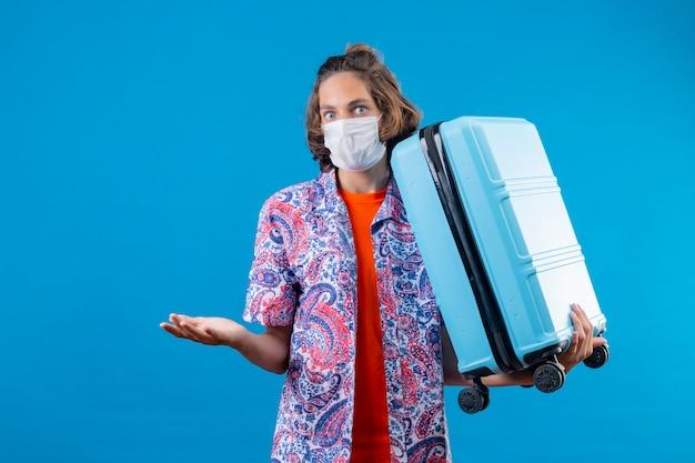 Giovane ragazzo bello che indossa la maschera protettiva per il viso tenendo la valigia di viaggio all'oscuro e confuso in piedi con le braccia alzate su sfondo blu