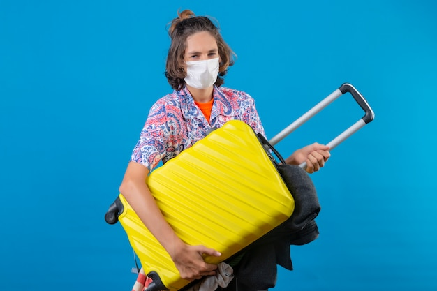 カメラを見て楽観的な笑顔立って服を着た旅行スーツケースを持って顔の防護マスクを着ている若いハンサムな男