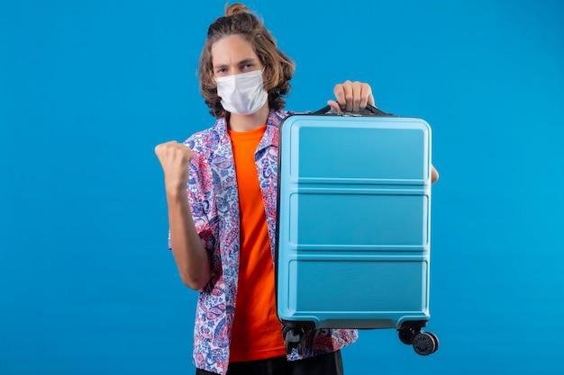 青い背景の上に立って幸せそうな顔の勝者の概念との勝利の後、拳を上げる旅行スーツケースを持って顔の防護マスクを着ている若いハンサムな男