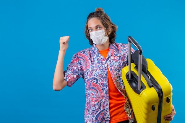 幸せな顔の勝者の概念に立って勝利後の拳を上げる旅行スーツケースを持って顔の防護マスクを着ている若いハンサムな男
