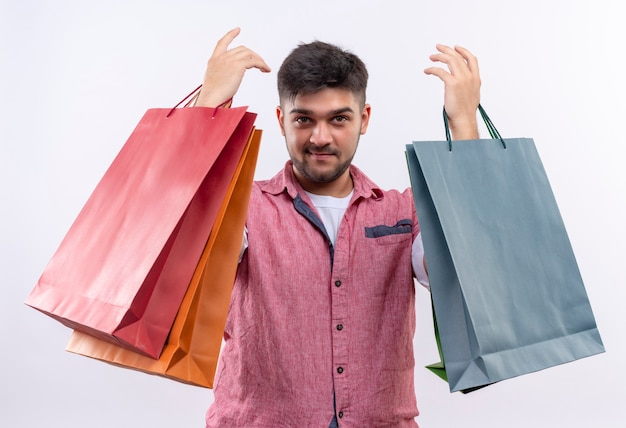 Young handsome guy wearing pink polo looking bragging about shopping shirt standing over white wall