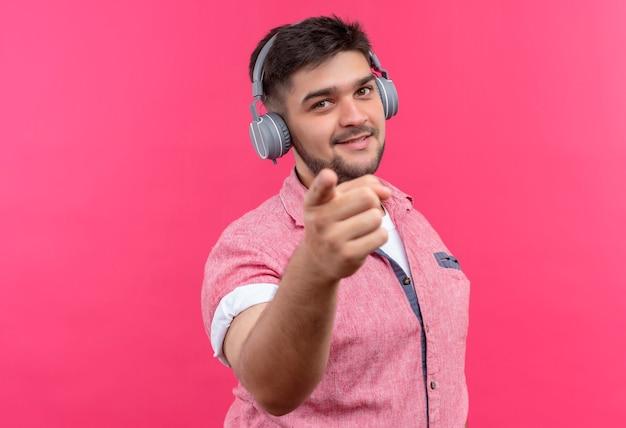 ピンクのポロシャツとピンクの壁の上に立っている人差し指で幸せに指しているヘッドフォンを身に着けている若いハンサムな男