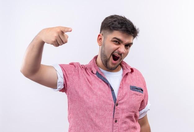 白い壁の上に立っている人差し指で怒って指しているピンクのポロシャツを着ている若いハンサムな男