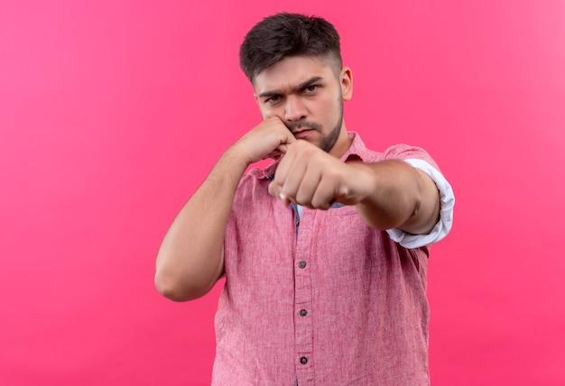 Giovane ragazzo bello che indossa la maglietta polo rosa con rabbia minacciando di colpire in piedi sopra il muro rosa