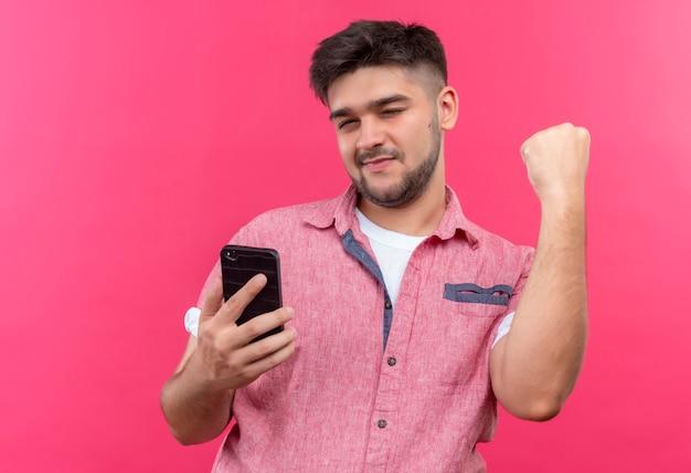 분홍색 벽 위에 전화를 들고 눈을 깜박이는 분홍색 폴로 셔츠를 입고 젊은 잘 생긴 남자