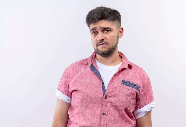 ピンクのポロシャツを着た若いハンサムな男は、白い壁の上に立って動揺して見える唇を噛んで混乱しました