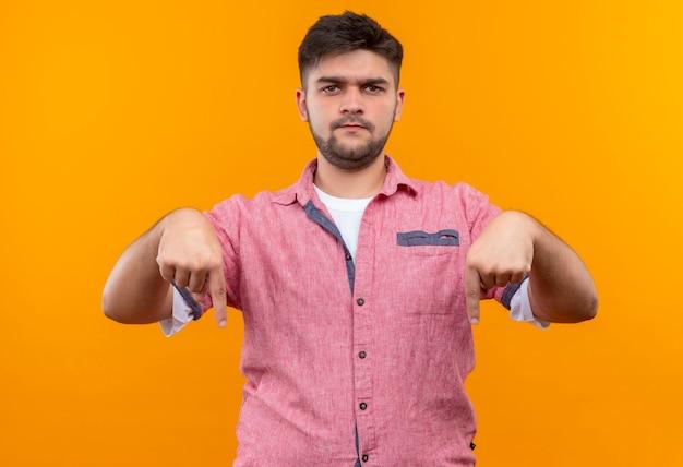 ピンクのポロシャツを着た若いハンサムな男は、オレンジ色の壁の上に立って人差し指を見て不機嫌になりました