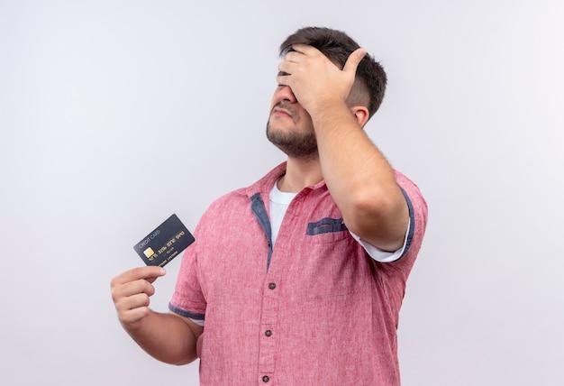白い壁の上に立っているクレジットカードを保持しているfacepalm動揺をしているピンクのポロシャツを着ている若いハンサムな男