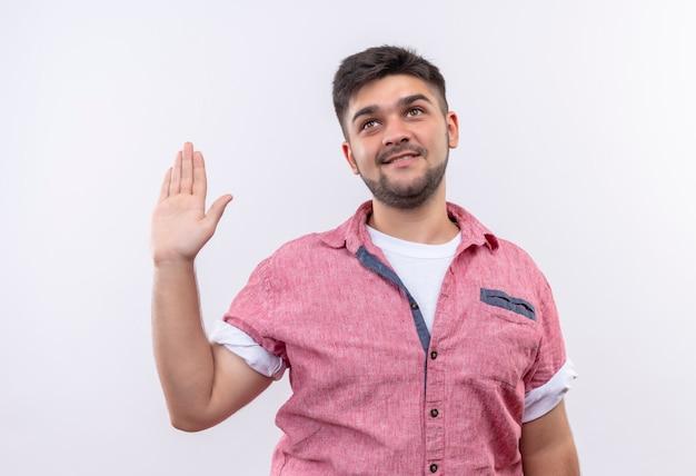 ピンクのポロシャツを着ている若いハンサムな男は白い壁の上に立っている上げられた左手で私の言葉のサインを与えます