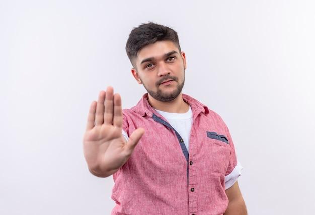 Молодой красивый парень в розовой рубашке поло делает знак остановки с рукой, стоящей над белой стеной