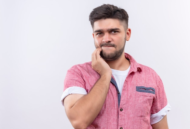 Young handsome guy wearing pink polo shirt doubtfully looking standing over white wall