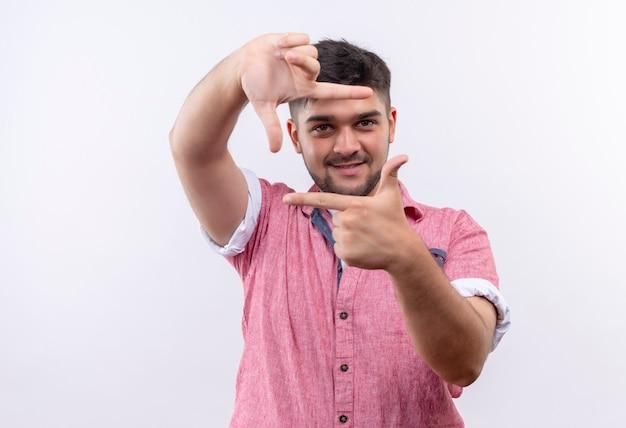 Молодой красивый парень в розовой рубашке поло радостно ловит кадр с указательными пальцами, стоящими над белой стеной