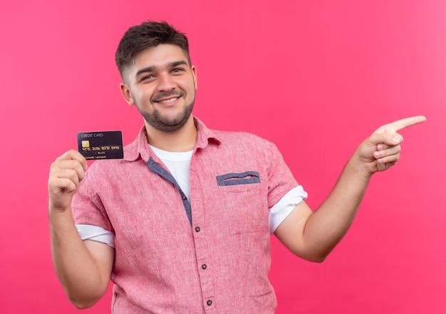 ピンクのポロシャツを着た若いハンサムな男は、ピンクの壁の上に人差し指が立っている左向きのクレジットカードを喜んで持っています
