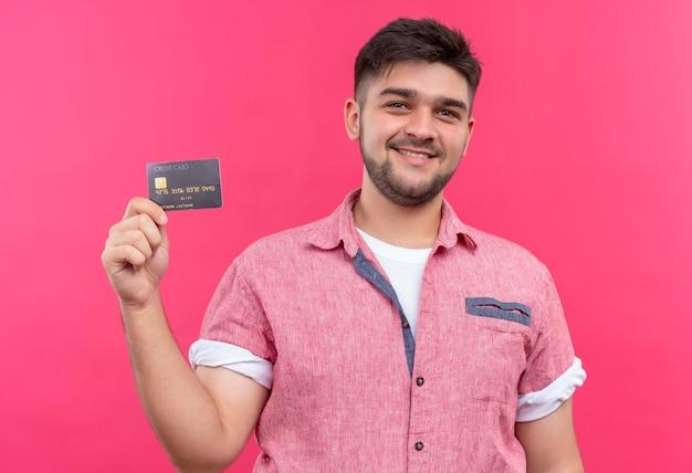 ピンクの壁の上に立っているクレジットカードを喜んで保持しているピンクのポロシャツを着ている若いハンサムな男