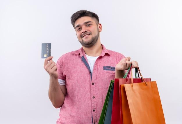 白い壁の上に立っているクレジットカードで買い物を喜んで探しているピンクのポロシャツを着ている若いハンサムな男