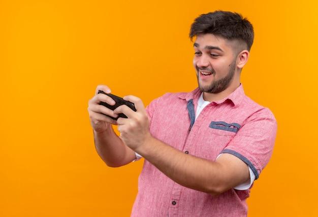 오렌지 벽 위에 서있는 전화에서 행복하게 놀고 분홍색 폴로 셔츠를 입고 젊은 잘 생긴 남자