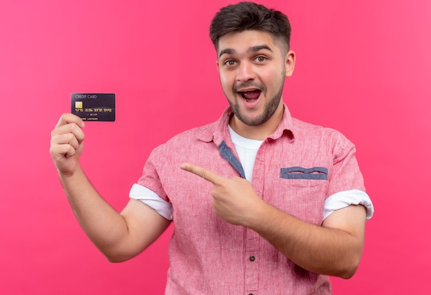 ピンクのポロシャツを着ている若いハンサムな男は、ピンクの壁の上に立っているクレジットカードを喜んで指しています
